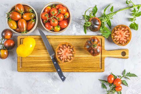 Slices raw fresh tomato. Colorful tomatoes and kitchen knife on wooden cutting board. Concept of green house life style and products of subsistence farming, flat lay on light gray concrete surface