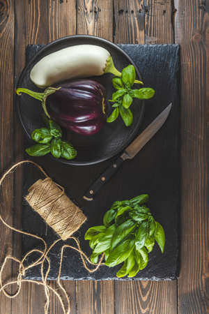 Raw fresh eggplant in ceramic plate on black stone cutting board. Concept of green house life style and products of subsistence farming, flat lay on dark wooden surface, copy space