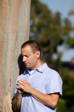 folded hands: Man praying with folded hands next to a tree.