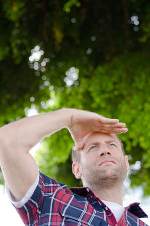 man looking out: Man looking out with hand on his forehead. Stock Photo