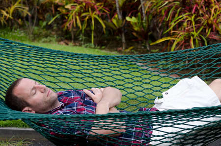people relax: Man sleeping in hammock with eyes closed and arms crossed. Stock Photo