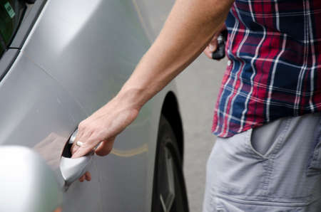 clicker: Man getting into silver car. Close up of hand on the door handle and other hand holding the clicker to unlock the door.