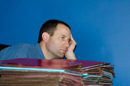 disdain: Man worn out at work looking straight ahead sitting in front of a large pile of files with his head leaning on his hand. Stock Photo