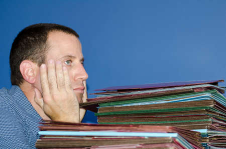 disdain: Man stressed out at work with hands on his face sitting in front of a large pile of files. Stock Photo
