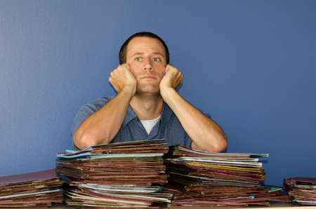 disdain: Man stressed at work looking straight ahead with his hands resting against his face. Stock Photo