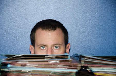 disdain: Man bored at work peeking over a large pile of files. Stock Photo