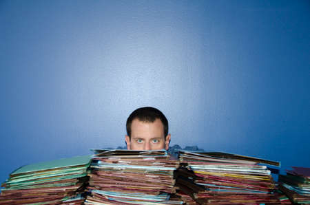 disdain: Hiding behind files at the office. Stock Photo