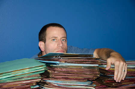 disdain: Man bored at work with too many files to review. Stock Photo