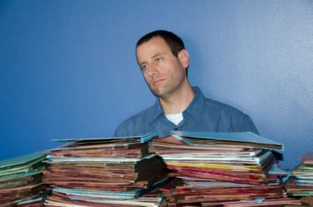 disdain: Man bored at work sitting in front of a large pile of files staring straight ahead.