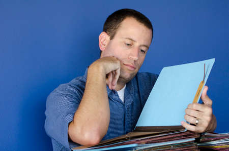 disdain: Man bored at work resting his head on his fist reviewing a file.