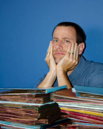 disdain: Man stressed at work gazing straight ahead with his hands on his cheeks. Stock Photo