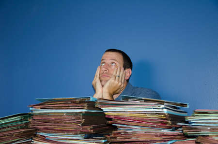 disdain: Man looking bored and stressed at work with his hands on his face looking up at the ceiling. Stock Photo