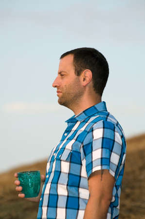 hillside: Man standing and looking out onto a hillside holding a cup in his hand wearing a plaid shirt. Stock Photo