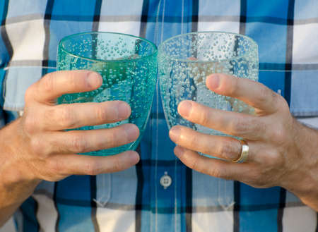 holding close: Close up of two hands holding two plastic cups with a plaid shirt in the background.