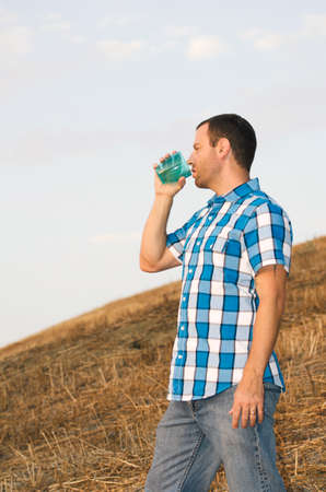 man looking out: Man looking out on a hillside while holding a plastic cup, wearing a plaid shirt and standing up.