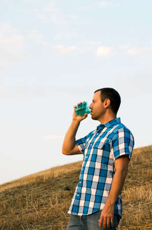 hillside: Man looking out on a hillside while holding a plastic cup, wearing a plaid shirt and standing up.