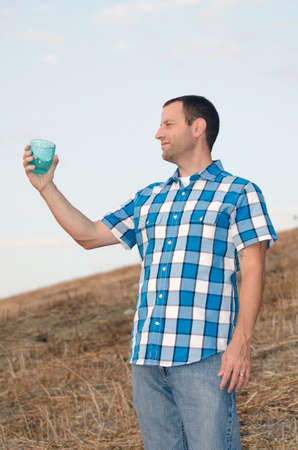 man looking out: Cheers! Man looking out on a hill side while holding a cup with his arm extended wearing a plaid shirt.