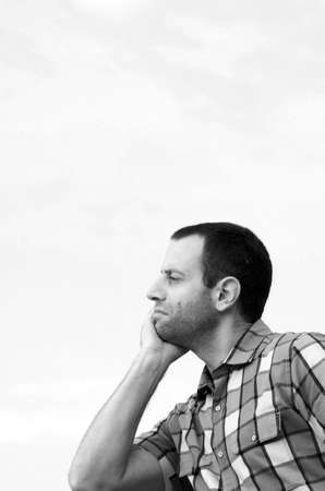 man looking out: Black and white photo of a man looking out with his face leaning against his hand wearing a plaid shirt.