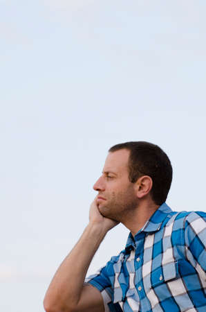 man looking out: Portrait of a man looking out with his face leaning against his hand wearing a plaid shirt.