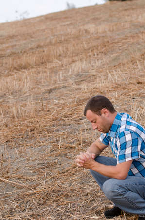 clasped hand: Man crouching down and praying with his hands clasped outside on a hill side wearing a plaid shirt. Stock Photo