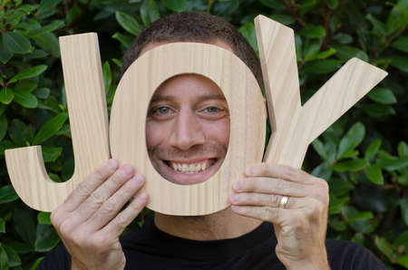 'hide out': Smiling man hiding in the O of the wooden letters of that spell the word joy.