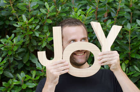 Man hiding behind the wooden letters of the word joy. Stock Photo