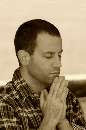 Man praying with hands together in sepia tone.