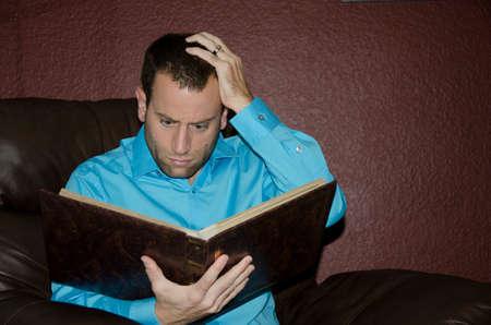 Homme choqué regardant un vieil album photo. Banque d'images - 67212685