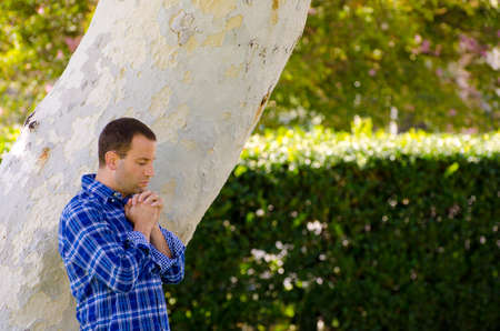 Man praying in a park by a large tree trunk.