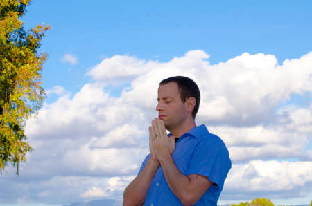 Man praying with the clouds and trees in the background.