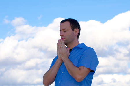 Man praying with the clouds in the background. Stock Photo