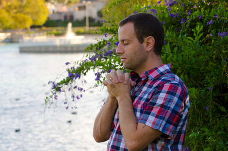 Man praying by a lake alone in front of a bush with flowers and a fountain in the background. Stock Photo