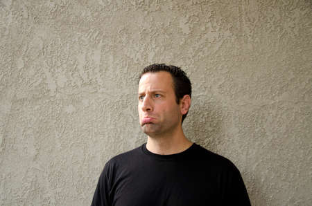 bummed: Man in a black t-shirt with a sad expression outdoors looking straight ahead.
