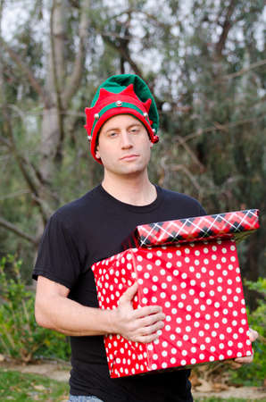 Man worn out by the Christmas season carrying gifts and wearing a Christmas hat.