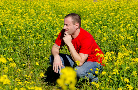 Man in a field of yellow flowers thinking of what tomorrow holds.