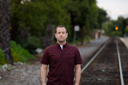 Man with a serious stern expression standing on the railroad tracks alone. Imagens - 74675062