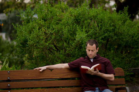 Man relaxing on a bench outside reading a book leaning back. Imagens