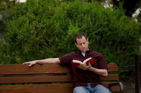 Man reading a book alone on a bench outside.