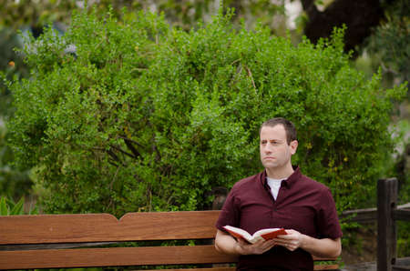 Man sitting outside alone on a bench holding an open book. Imagens - 74794451
