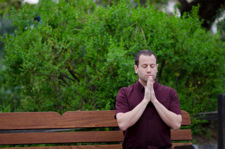 Man praying on a bench with his hands together. Stock Photo
