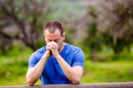 Man praying with his head down and hands together, alone in nature embracing God`s creation. Stock Photo