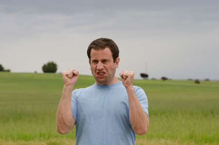 tensed: Angry man outdoors with clenched fists with a grassy field behind him.
