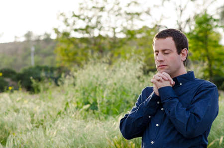 Man praying alone outside in a grassy field with hands folded and eyes closed.