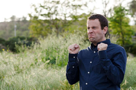 not open: Angry man outdoors with fist clenched making an angry face. Stock Photo