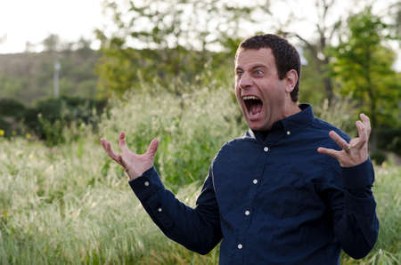 Man screaming in anger with hands out and mouth wide open Stock Photo