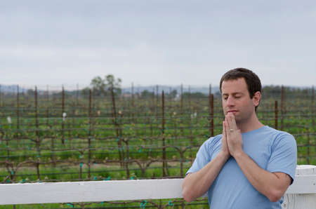 Man praying in front of farmland alone.
