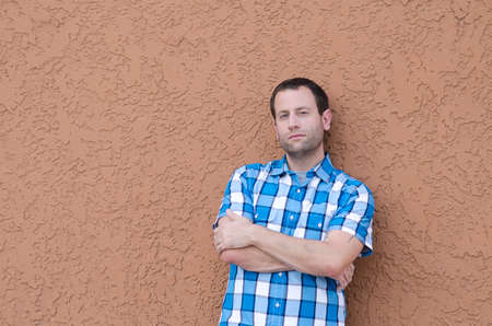 Portrait of a man leaning to the side with arms crossed against neutral background. Stock Photo