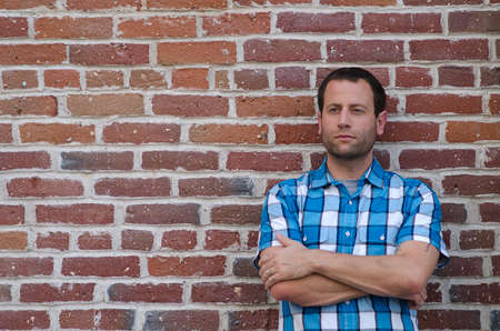 Portrait of a man leaning against a brick wall with her arms crossed. Stock Photo