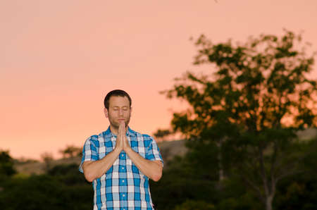 Man praying alone at dusk with pink skies in the background.