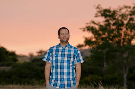 Man in a plaid blue shirt with hands in his pockets at sunset looking off to the right and trees in the background.